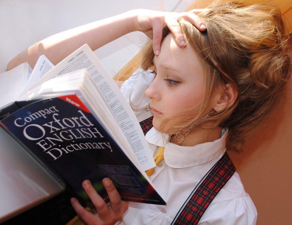Ragazza che sfoglia il Compact Oxford English Dictionary e ha paura delle lingue straniere